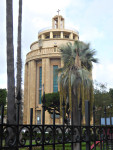 A tall circular pale stone tower which is a war memorial in central Palermo is shown behind a park with Palm trees.